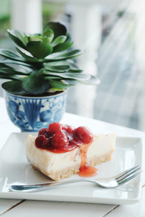 Köstlich mit Nachtisch ein Stück Kirschkäsekuchen und schwarzen Kaffee auf weißem Tonholztisch lizenzfreie stockbilder