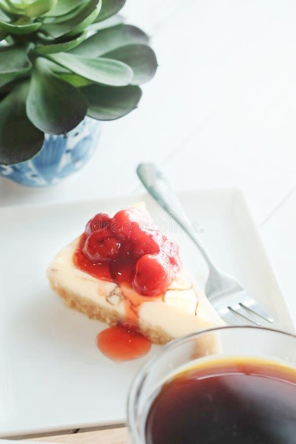 Köstlich mit Nachtisch ein Stück Kirschkäsekuchen und schwarzen Kaffee auf weißem Tonholztisch lizenzfreies stockbild