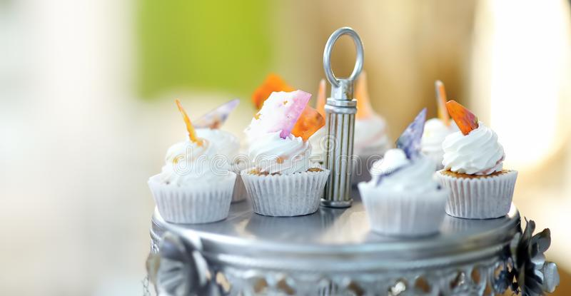 Köstliche bunte Heiratskleine kuchen mit Blume und Schmetterling und schöner glasig-glänzender Kuchen lizenzfreies stockfoto