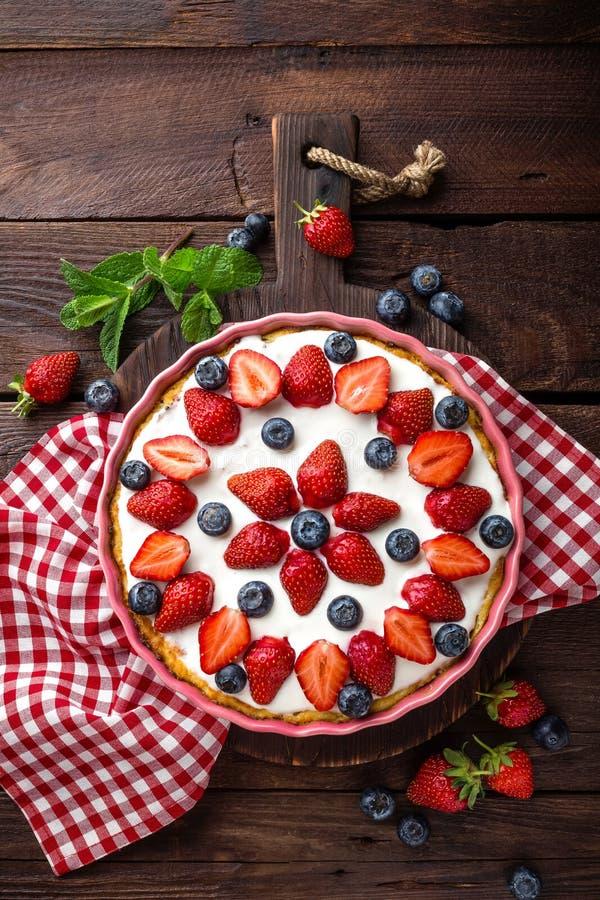 Köstliche Erdbeertorte mit frischer Blaubeere und Schlagsahne auf hölzerner rustikaler Tabelle, Käsekuchen lizenzfreies stockbild