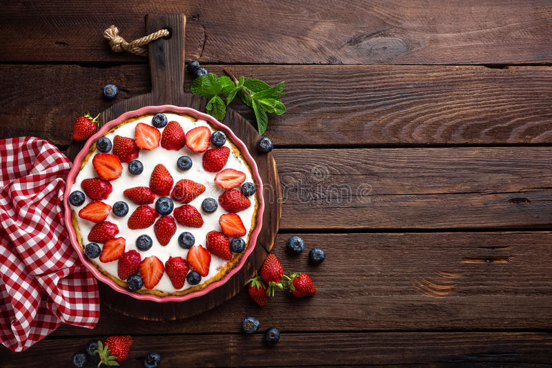 Köstliche Erdbeertorte mit frischer Blaubeere und Schlagsahne auf hölzerner rustikaler Tabelle, Käsekuchen stockfotografie