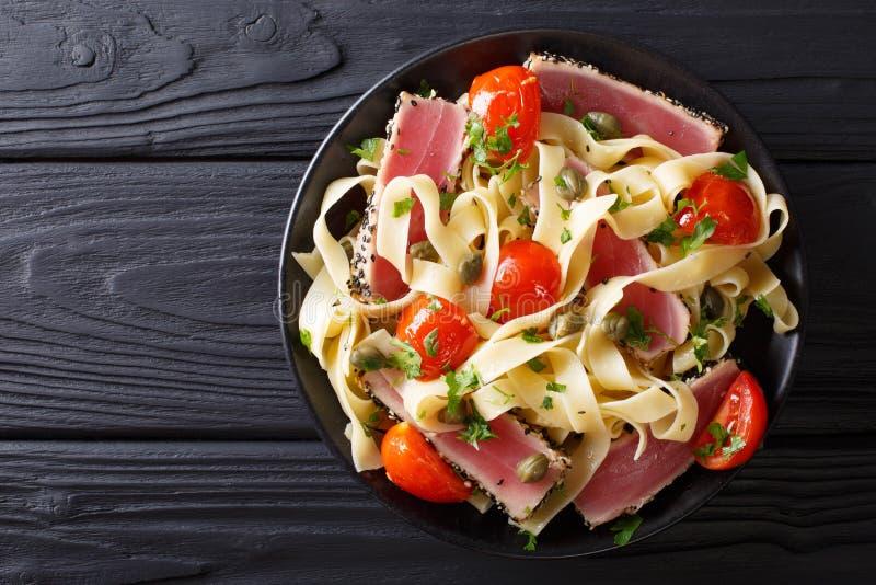 Köstliche Fettuccineteigwaren mit Thunfischsteak, -tomaten und -kapriolen stockbild