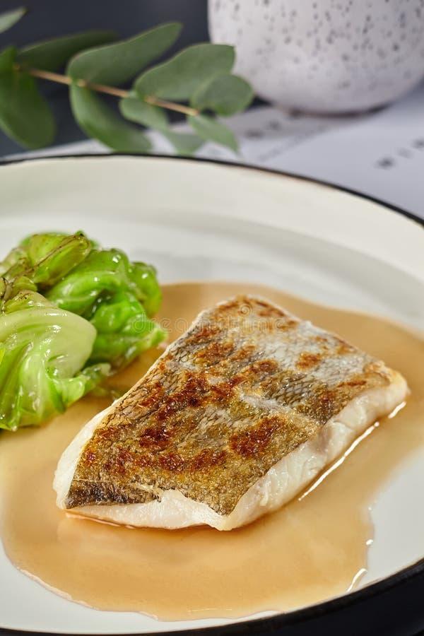 Köstliche Fische kochten in einem Ofen und mit Soße und Kohl geschmückt stockfotos