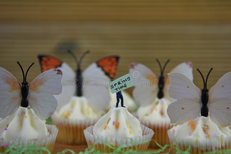 Köstliche Frühjahrkleine kuchen überstiegen mit Dekorationen von Schmetterlingsformen auf einem rustikalen hölzernen Hintergrund stockbild