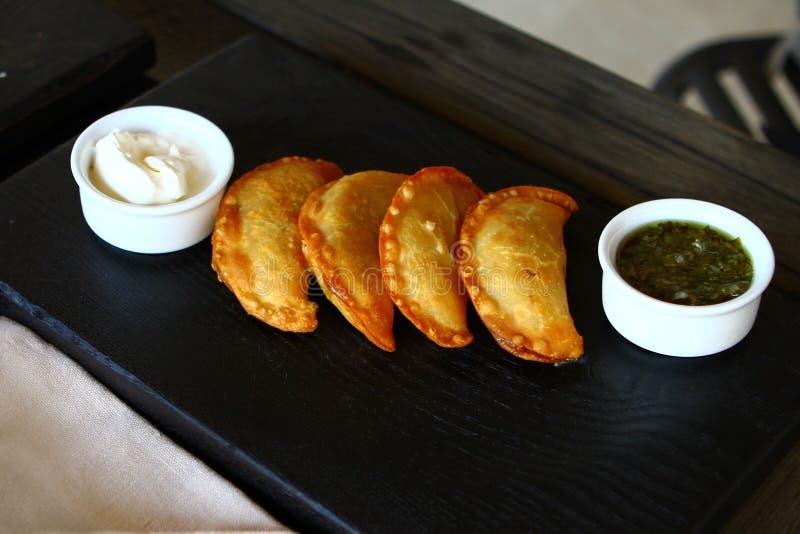 Köstliche gebratene cheburek Torten auf der dunklen Platte mit zwei Soßen stockfoto
