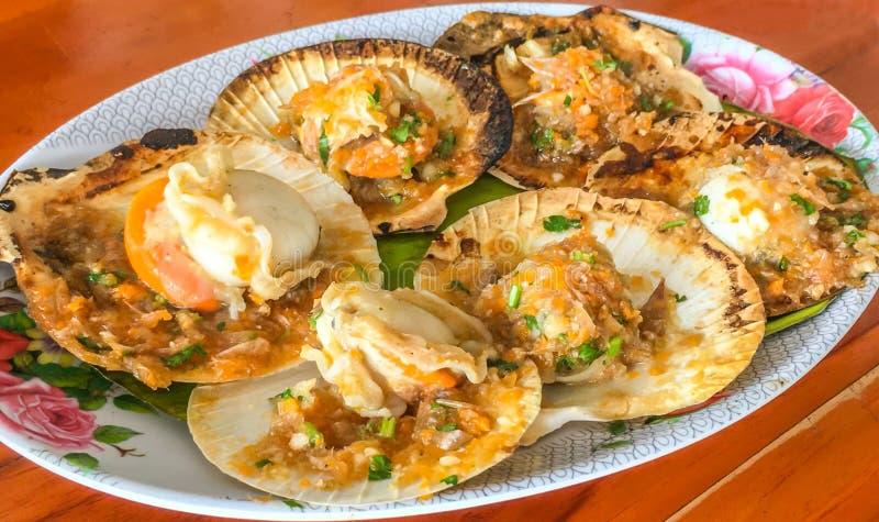 Köstliche gegrillte Kamm-Muscheln der Nahaufnahme mit Butter und würziger Soße auf dem Oberteil auf hölzernem Tabellenhintergrund lizenzfreie stockbilder