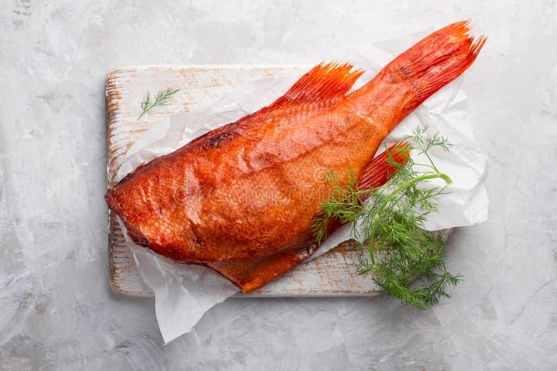 Köstliche geräucherte Fische (Seebarsch) auf hölzernem Hintergrund lizenzfreie stockbilder