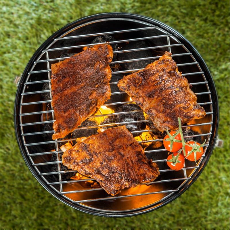 Köstliche Gestelle der Rippe grillend über einem BBQ-Feuer lizenzfreies stockbild