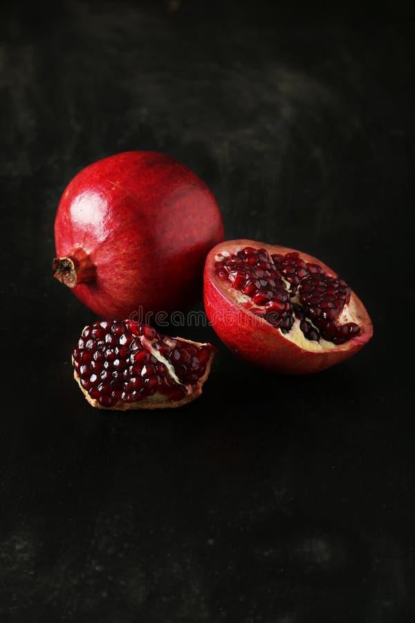 Köstliche Granatapfelfrucht auf dem schwarzen Hintergrund lizenzfreie stockfotografie