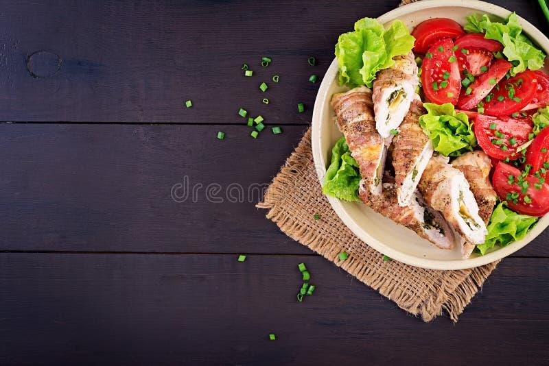 Köstliche Hühnerrollen angefüllt mit dem Käse und Spinat eingewickelt in den Streifen des Speckes lizenzfreies stockbild