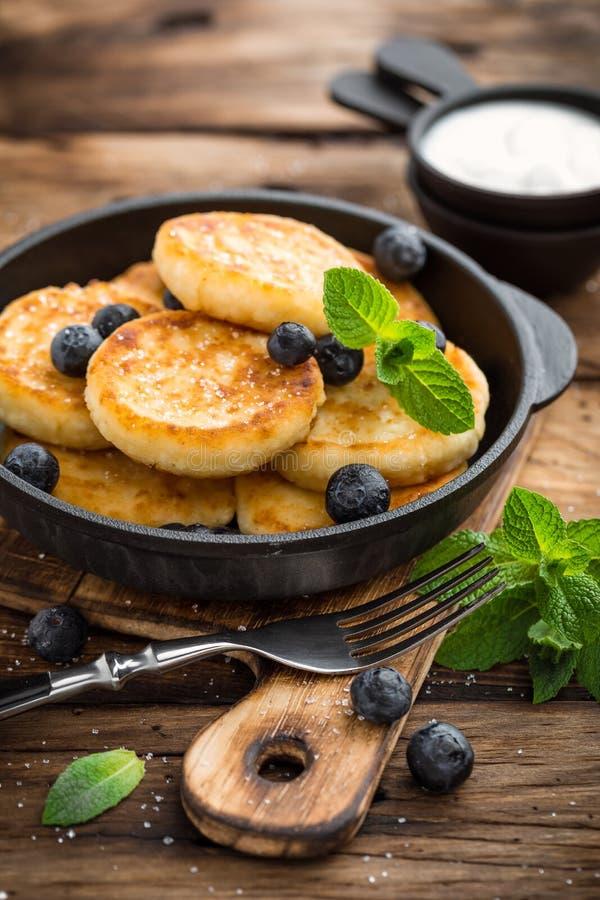 Köstliche Hüttenkäse Pfannkuchen oder syrniki mit frischer Blaubeere in der Gusseisenwanne auf dunklem hölzernem rustikalem Hinte lizenzfreies stockbild