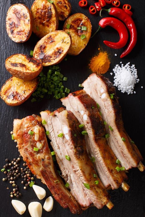Köstliche Mahlzeit: gebratene Rippen mit Ofenkartoffeln und Gewürzen nah stockbild