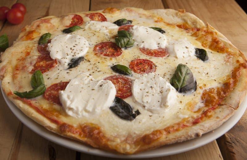 Köstliche Mozzarellapizza auf einem Holztisch stockfotos