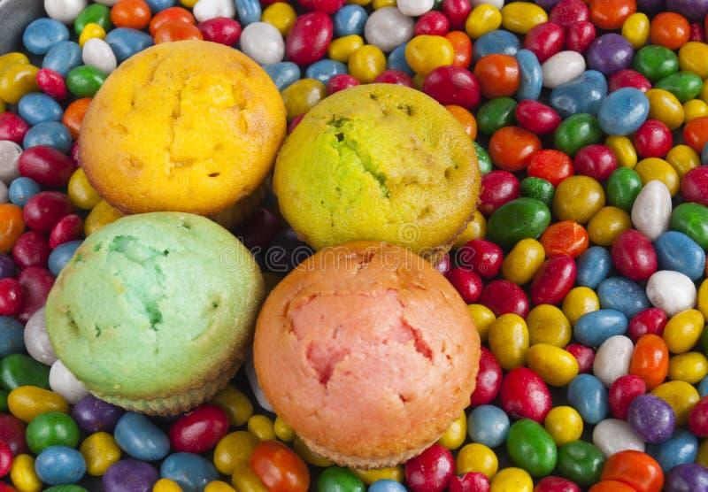 Köstliche Muffins auf einem Hintergrund der bunten Süßigkeit stockfotos