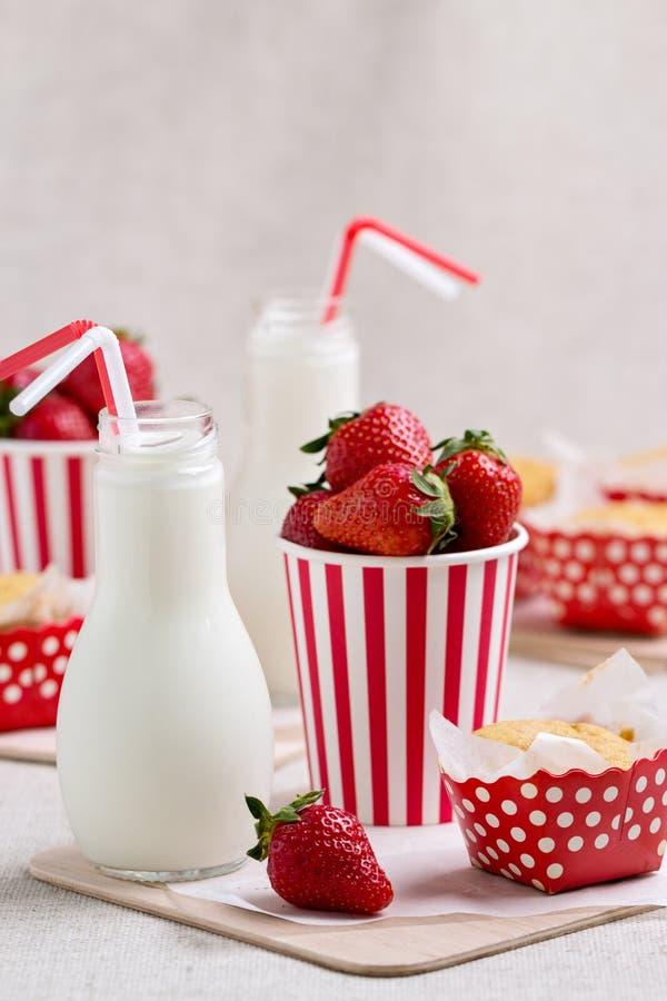 Köstliche Muffins, Erdbeeren und Milch in den Flaschen stockfoto