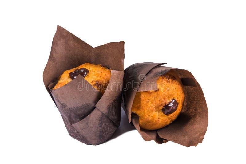 Köstliche Muffins mit der Schokolade, die die braune Verpackung, weißer Hintergrund, Nahaufnahme ausfüllt lizenzfreies stockfoto