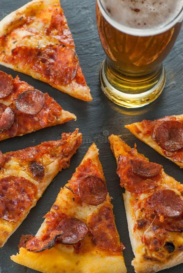 Köstliche neue gekochte Scheiben der Pepperonipizza auf Schiefer und des Glases Bieres stockbilder