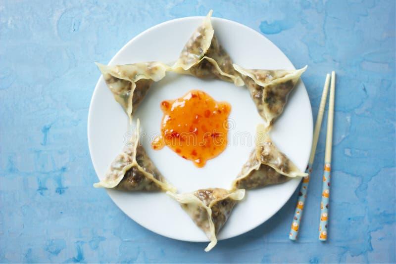 Köstliche orientalische Dim Sum-Mehlklöße mit blauen Essstäbchen stockfoto