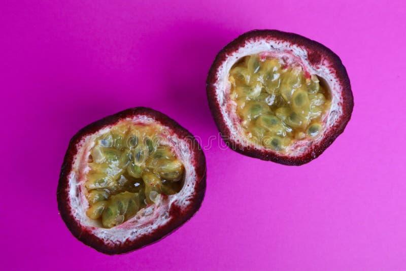 Köstliche Passionfruit-Hälften mit einem hellen Pink-Hintergrund stockfoto