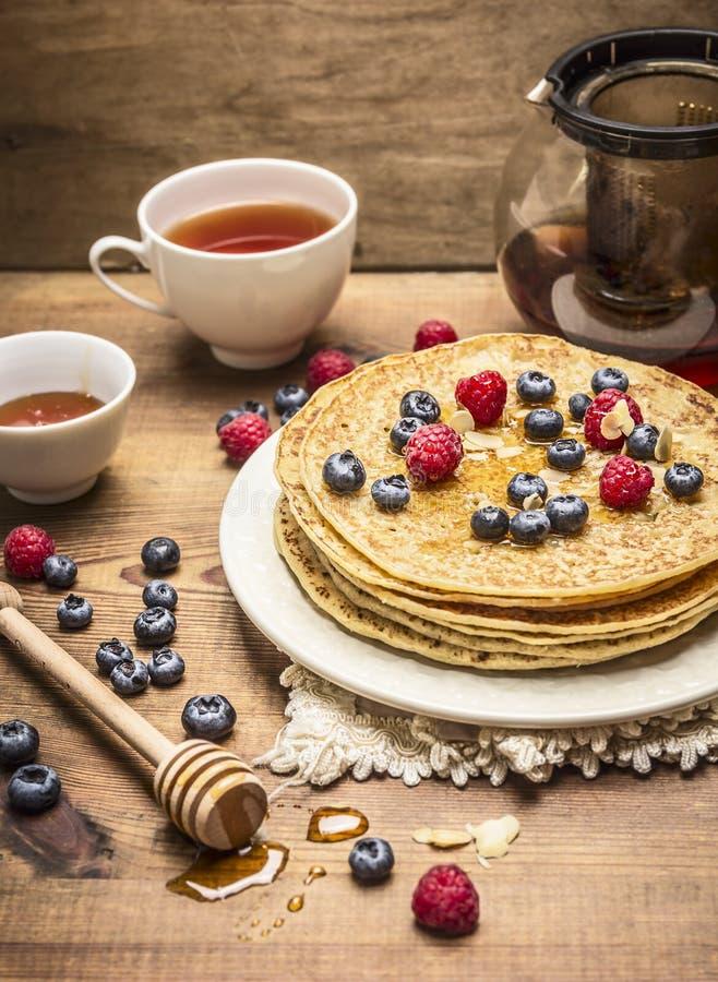 Köstliche Pfannkuchen mit frischen Beeren auf einer weißen Platte mit Honiglöffel und Tasse Tee auf hölzernem Hintergrundabschluß lizenzfreie stockbilder