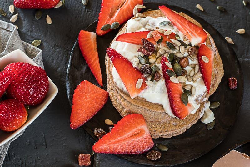 Köstliche Pfannkuchen mit Jogurterdbeeren und -samen stockbild