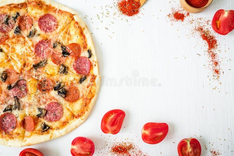 Köstliche Pizza mit Bestandteilen und Gewürzen auf weißem rustikalem Hintergrund Flache Lage, Draufsicht lizenzfreie stockfotos