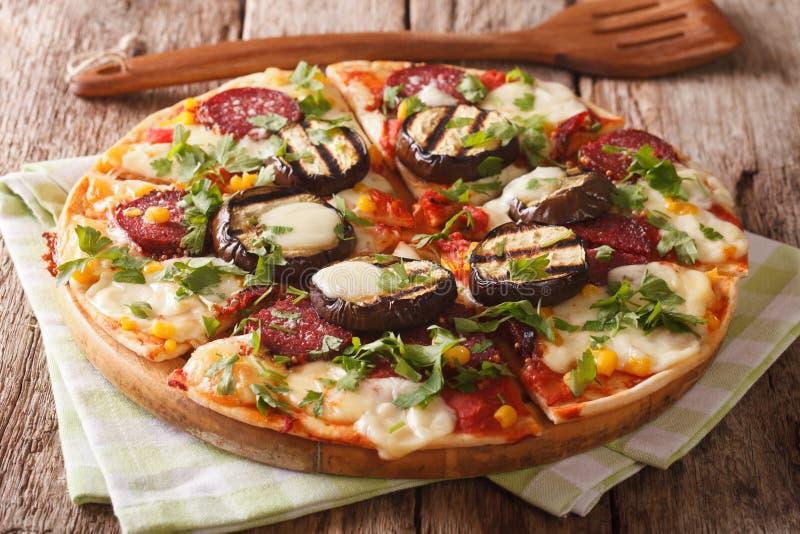 Köstliche Pizza mit gegrillter Aubergine, Wurst, Kräutern und Käse stockfotografie