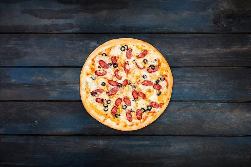 Köstliche Pizza mit geräucherter Wurst und Oliven auf einem dunklen hölzernen Hintergrund Draufsichtmitteorientierung stockbilder