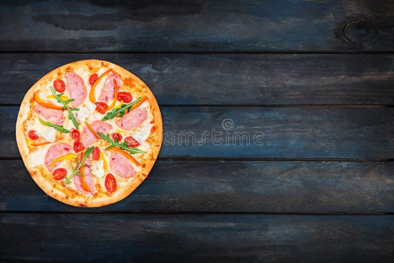 Köstliche Pizza mit Schinken, Gemüsepaprika, rucola, Tomaten und Eisbergsalat Draufsichtorientierung auf der linken Seite stockbilder