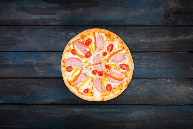 Köstliche Pizza mit Schinkengemüsepaprikas und -tomaten auf einem dunklen hölzernen Hintergrund Draufsichtmitteorientierung stockfoto