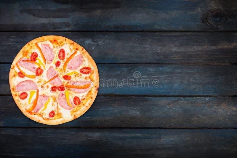 Köstliche Pizza mit Schinkengemüsepaprikas und -tomaten auf einem dunklen hölzernen Hintergrund Draufsichtorientierung auf der li stockfotos