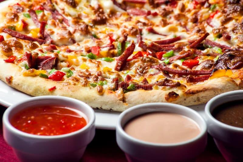 Köstliche Pizza mit mit Soßen auf dem Tisch Chef gie?t Oliven?l ?ber frischem Salat in der Gastst?ttek?che lizenzfreie stockbilder