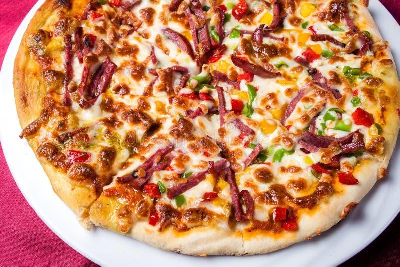 Köstliche Pizza mit mit Soßen auf dem Tisch Chef gie?t Oliven?l ?ber frischem Salat in der Gastst?ttek?che lizenzfreies stockfoto