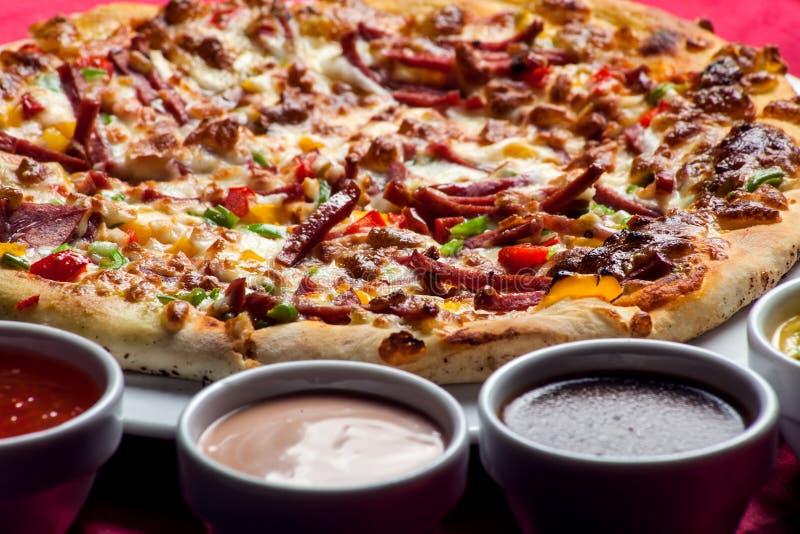 Köstliche Pizza mit mit Soßen auf dem Tisch Chef gie?t Oliven?l ?ber frischem Salat in der Gastst?ttek?che stockbilder