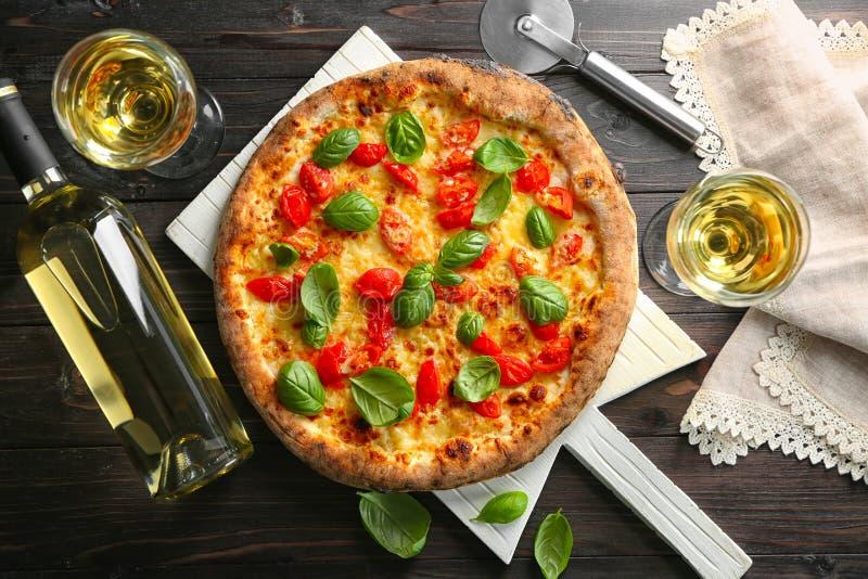 Köstliche Pizza mit Wein auf Tabelle lizenzfreie stockfotografie