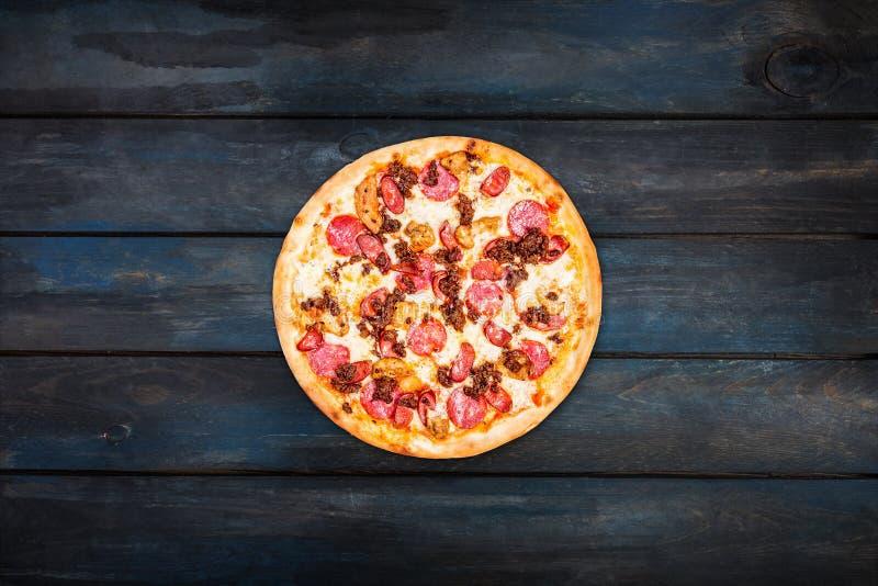 Köstliche Pizzafleischmischung mit geräucherter Wurst, Huhn, Hackfleisch und Pepperonis auf einem dunklen hölzernen Hintergrund stockbild