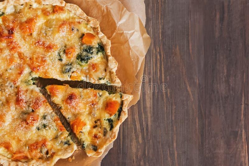 Köstliche Quiche oder Torte mit Gemüse, Spinat und Käse auf dem rustikalen Holztisch stockbild