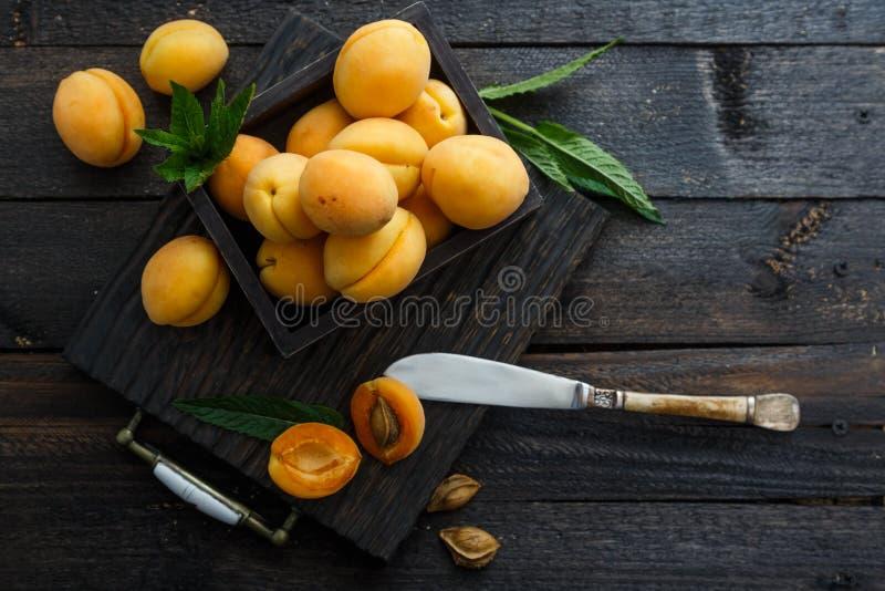 Köstliche reife Aprikosen in einer Holzkiste auf dunklem hölzernem Hintergrund, rustikale Art stockfotografie