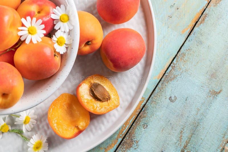 Köstliche reife Aprikosen in einer Schüssel auf dem Holztisch Nahaufnahme mit Aprikosen und Gänseblümchenblumen stockbild