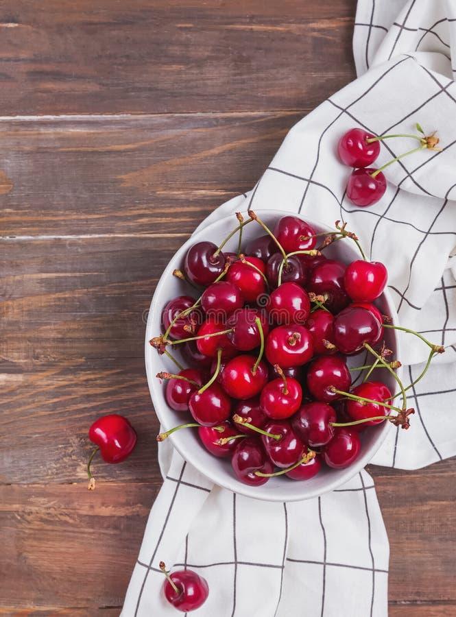 Köstliche reife Kirschen in einer Schüssel auf dem Holztisch lizenzfreies stockfoto
