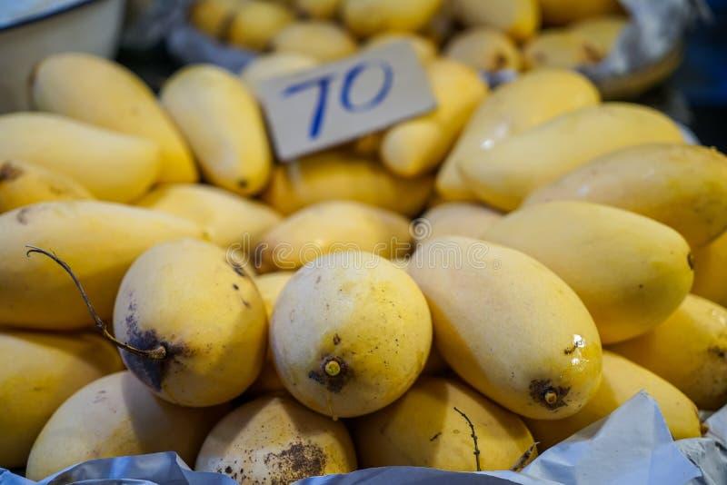 Köstliche reife oder süße gelbe Mangosaisonalfrucht frisch vom Garten, der natürliche Narbe zeigt und Saft, der mit Preis verkauf stockfoto