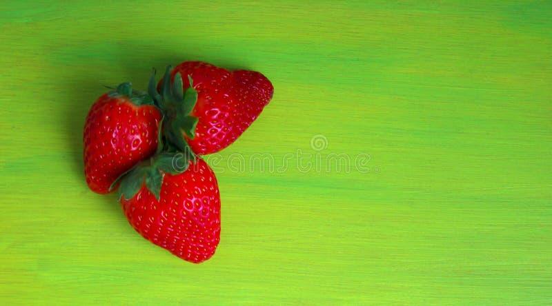 Köstliche rote Erdbeere auf einem grünen Hintergrund stockfotos