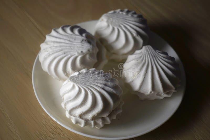 Köstliche Süßspeisen des Eibisches vier des weißen Eibischzefirs auf einer Platte demgegenüber, die auf einem Holztisch beleuchte lizenzfreie stockbilder