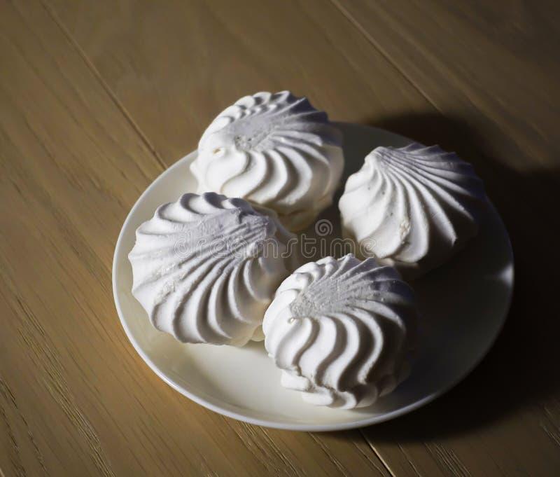 Köstliche Süßspeisen des Eibisches vier des weißen Eibischzefirs auf einer Platte demgegenüber, die auf einem Holztisch beleuchte lizenzfreie stockfotografie