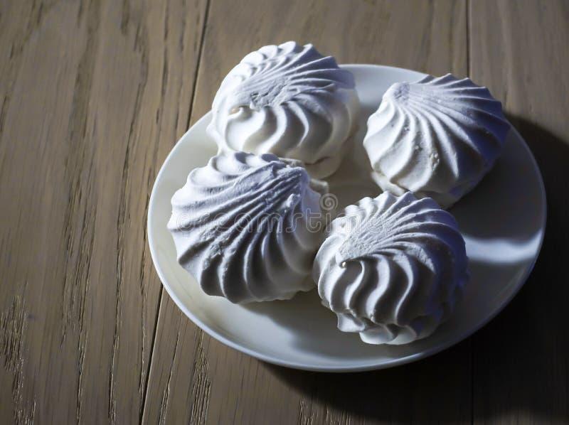 Köstliche Süßspeisen des Eibisches vier des weißen Eibischzefirs auf einer Platte demgegenüber, die auf einem Holztisch beleuchte stockbild