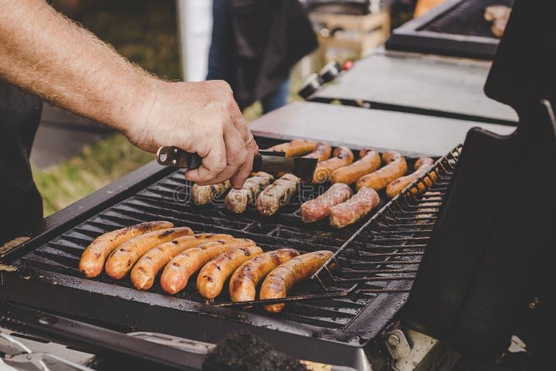 Köstliche saftige Fleischwürste auf dem großen Grill grillen im Freien lizenzfreies stockbild