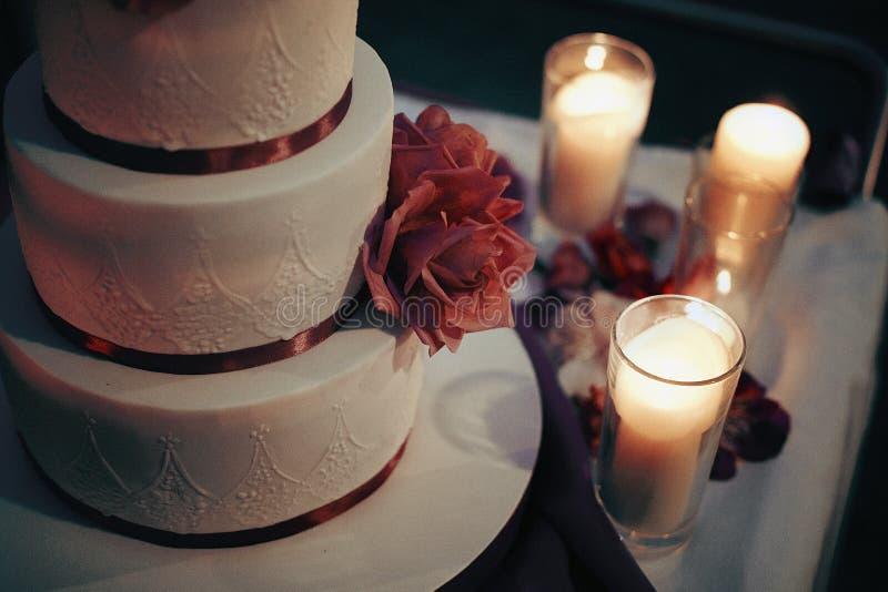 Köstliche schöne weiße Hochzeitstorte mit purpurroten Blumen u. kann stockfotos
