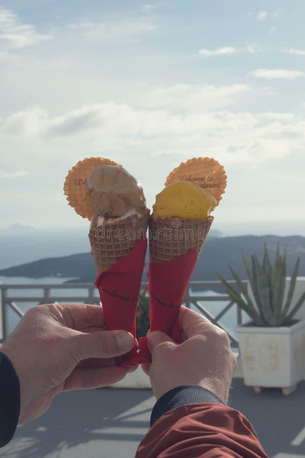Köstliche Schokoladen- und MangoEiscreme in den Waffelschalen vor dem hintergrund des Meeres und der Berge stockbild
