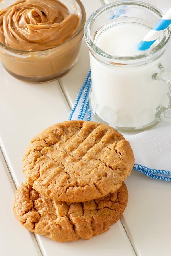 Köstliche selbst gemachte Erdnussbutterplätzchen mit Becher Milch Weißer hölzerner Hintergrund Gesunder Snack oder geschmackvolle lizenzfreies stockfoto