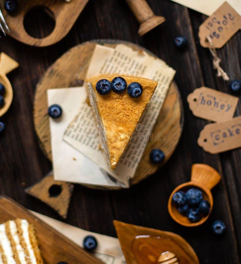 Köstliche selbst gemachte Scheiben russischen Honigkuchen medovik mit weißer Creme, Blaubeeren auf die Oberseite auf hölzernen stockfotos